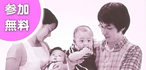 若い夫婦がそれぞれ乳児を抱え、微笑みかける画像
